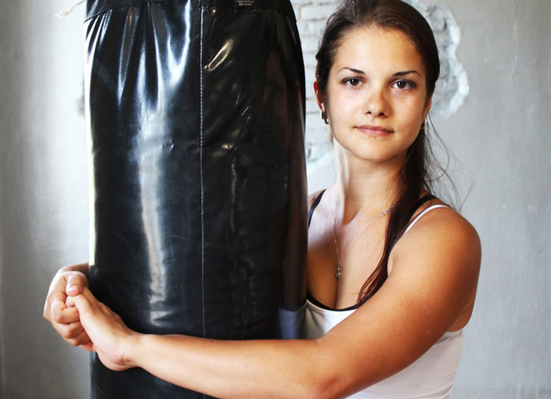 Photo of a WingTsun student hugging a heavy bag.